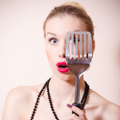 Surprised pinup woman looking through spatula