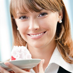 Smiling businesswoman with cake at office