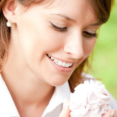 Smiling woman with cake outdoor