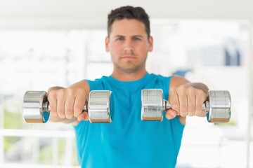 Sporty young man with dumbbells in gym