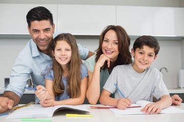 Smiling couple helping kids with homework at home