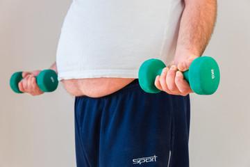 Übergewichtiger Mann trainiert mit Hanteln