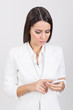 Attractive young businesswoman wearing white using smart phone