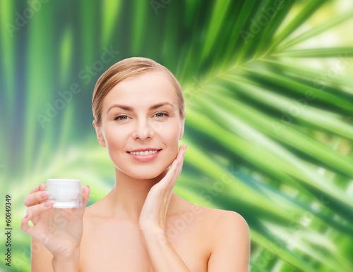 woman applying cream on her skin