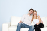 Young beautiful couple on a sofa at home
