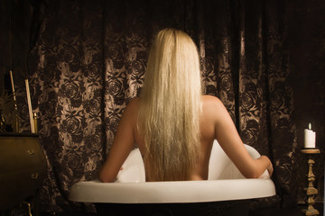 Naked girl takes a bath in vintage interior