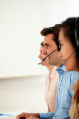 Man and women operator working with headphones