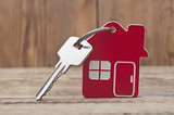 Symbol of the house with silver key on wooden background