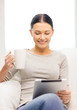 smiling woman with tablet pc computer and cup