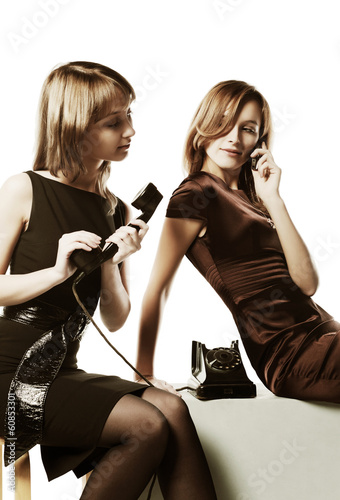 Two young women with a retro and mobile phones