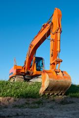 Big orange excavator resting on grass after a hard day's work
