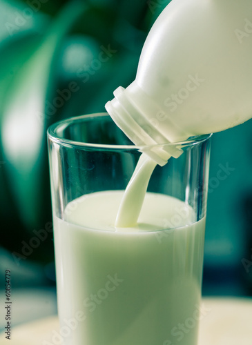 milk poured in glass cup over indoors background