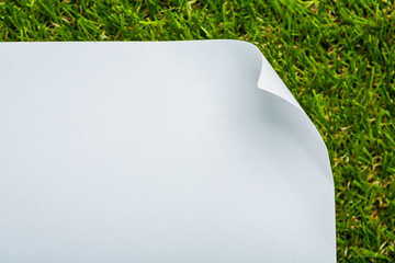 Blank paper on green grass background