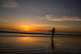 Surfer walks out the ocean at sunset