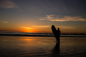 Surfer stand with surf board at sunset