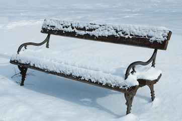 Snowy bench in the park, soft blue tone