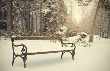 Vintage photo of a snowy bench in park