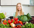 woman with pile of raw vegetables in home