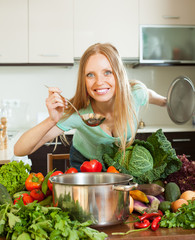 positive  woman cooking with ladle from raw vegetables