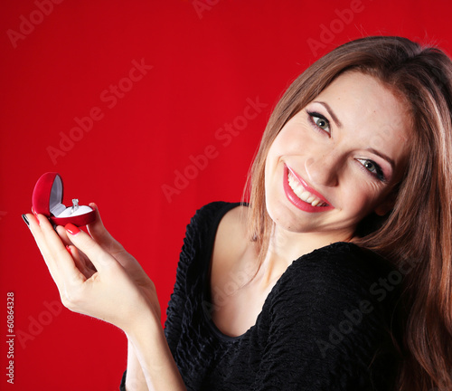 Girl looks at box with wedding ring on color background