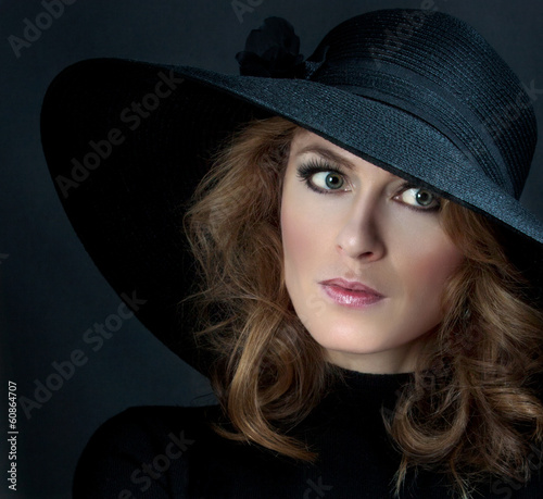 portrait of a woman in elegant hat on a black background