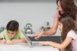 Mother with kids using laptop in kitchen