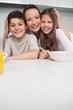 Portrait of a smiling mother with kids in kitchen