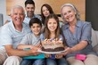 Portrait of extended family with cake in living room