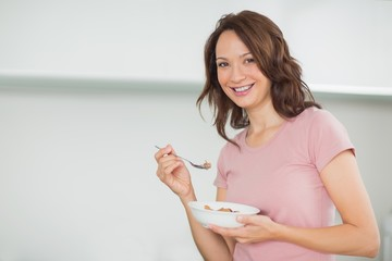 Portrait of smiling woman with a bowl of cereals at home