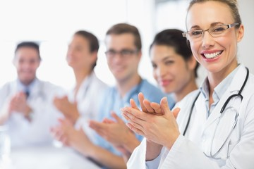 Happy doctor and team clapping