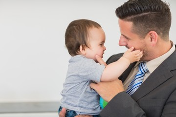 Businessman touching cheek of baby boy