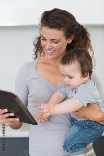 Mother looking at digital tablet while carrying baby