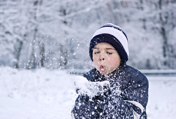 Niño soplando nieve de sus manos