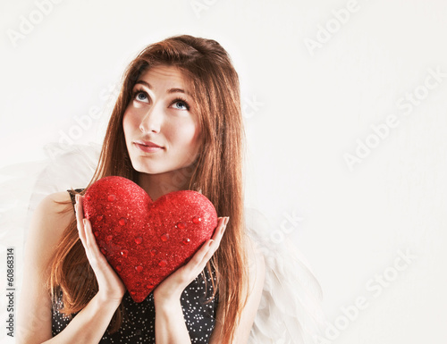 Portrait of dreaming girl as angel with red heart