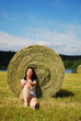 Woman sitting down the stubble-field