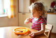 Little cute girl eating spaghetti