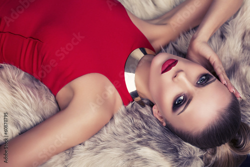 beautiful woman in red dress lying on fur