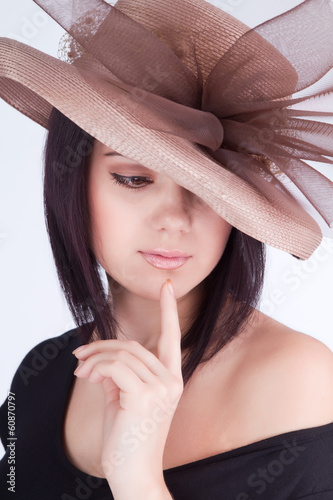 Portrait of girl in hat finger near lips look down