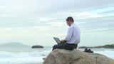 Geschäftsmann arbeitet mit Laptop am Strand