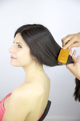 Beautiful woman getting long hair brushed with wood brush