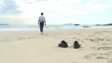 Geschäftsmann geht barfuß am Strand
