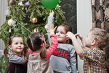 Children playing near the christmas tree