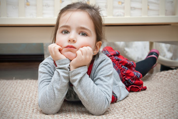 Little girl lying down on the floor of the childroom