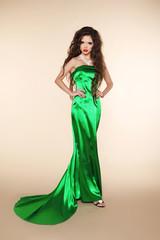 Fashion beautiful young woman posing in green dress with train o