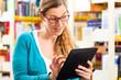 Mädchen in Bibliothek liest und lernt