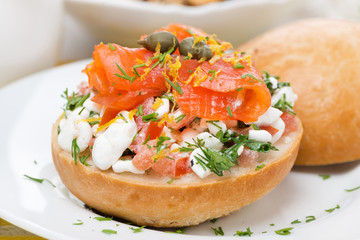 bun with cottage cheese, herbs, tomato and salmon, close-up