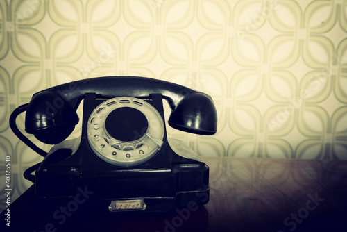 retro phone is on wooden table over vintage wallper