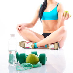 Fitness woman holding an apple with water, dumbbells and measuri