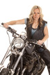 Woman leather vest sit on motorcycle look serious