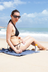 Frau im Badeanzug cremt sich ein